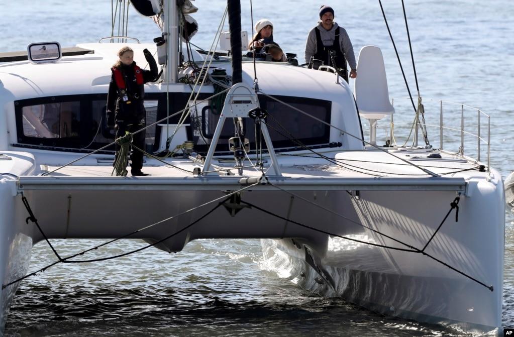 Climate activist Greta Thunberg waves as she arrives in Lisbon, Portugal, on the sailboat La Vagabonde.