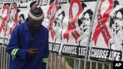 Seorang pria melewati poster Hari AIDS Sedunia di gedung perkantoran di Sandton, Johannesburg, Afrika Selatan, 1 Desember 2014.
