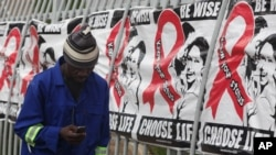A man makes a call on a mobile phone as he passes past a World AIDS Day banners on the perimeter of an office building in Sandton, Johannesburg, South Africa, Dec. 1, 2014. (AP Photo/Denis Farrell)