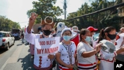 Demonstrators in ethnic Chin attire flash a three-fingered symbol of resistance during a protest against the recent military coup in Yangon, Myanmar Thursday, Feb. 11, 2021.