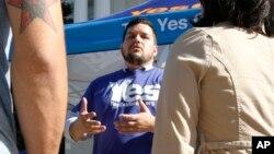 Marcus Ruiz Evans, centro, activista por la propuesta The Yes California Independence Campaign, trata de conseguir firmas de apoyo para la independencia de California.
