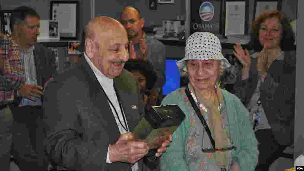 Leo Sarkisian, with his wife Mary looking on, enjoys a gift presented to him by colleagues at his retirement party.