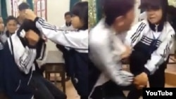 """Một đoạn clip cho thấy một nữ sinh cấp 3 giật tóc, tát và cầm chổi """"tấn công"""" một nam sinh cùng lớp."""
