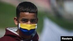 Un manifestante usa una máscara facial con los colores de la bandera colombiana durante una protesta que exige ayuda alimentaria del gobierno para los pobres, en medio del brote de la enfermedad del coronavirus.