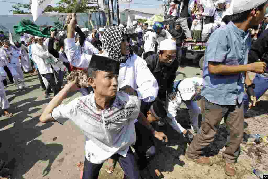 Seorang pria bersiap melemparkan batu ke arah polisi pada aksi protes menentang pembangunan gereja Katolik di Bekasi, Jawa Barat. Polisi menembakkan gas air mata ke arah demonstran.