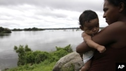 An indigenous woman holds her child near the Xingu River at the Araras tribe, near Altamira, northern Brazil, April 28, 2010. After nearly three decades of sometimes violent protests, about 1,000 other indigenous people in the remote region have resigned