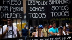 People protest with signs representing a jail during a rally in support of Leopoldo Lopez in Caraca.