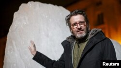 "Olafur Eliasson, a Danish-Icelandic artist, poses in front of a block of ice that was havested in Greenland and transported in a refrigerated container for a project called ""Ice Watch,"" in Paris, France, Dec. 3, 2015"