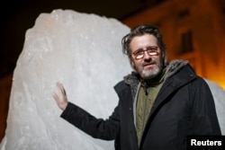 "FILE - Olafur Eliasson, a Danish-Icelandic artist, poses in front of a block of ice that was havested in Greenland and transported in a refrigerated container for a project called ""Ice Watch Paris,"" in Paris, France, Dec. 3, 2015"