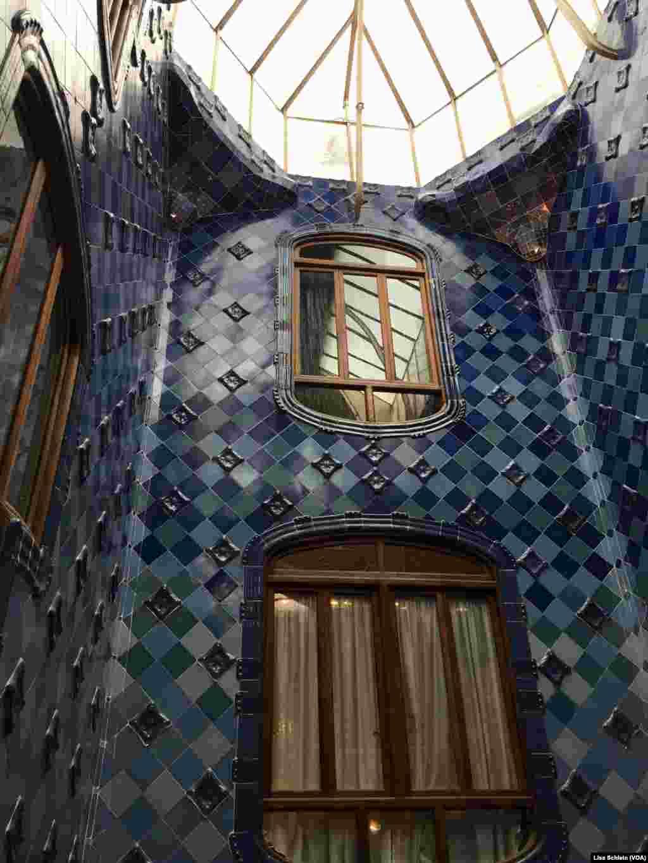 A large skylight illuminates the dark blue tiles of the upper floor of Casa Batllo, in Barcelona.