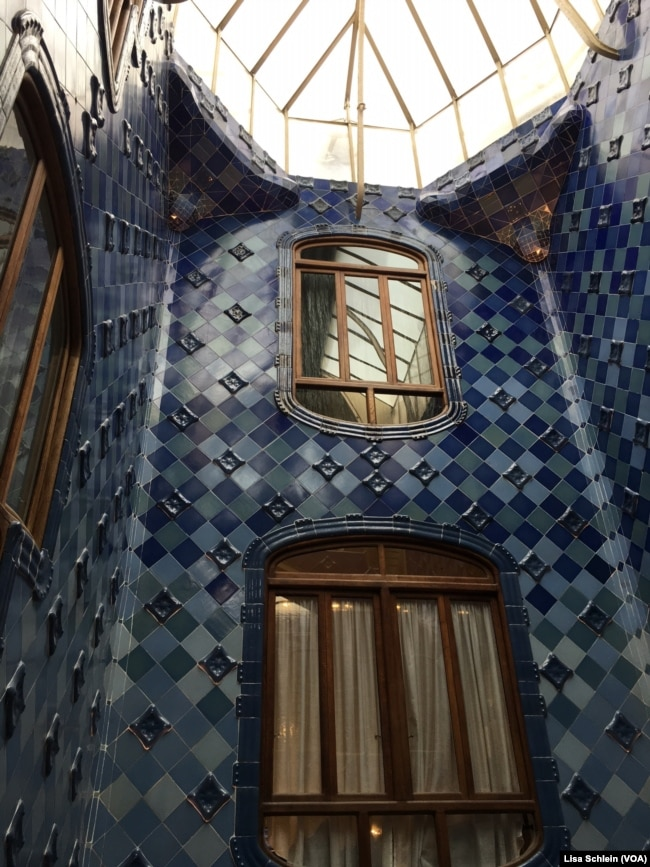 a large skylight illuminates the dark blue tiles of the upper floor of casa batllo