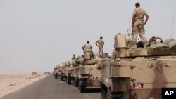 In this photo taken on Monday, Aug. 3, 2015, fighters against Shiite rebels known as Houthis stand on their armored vehicles on a road leading to Al-Anad base near Aden in the southern province of Lahej, Yemen.