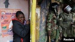 Une femme se cache et pleure à côté à des policiers lors des manifestations après la proclamation de la victoire du président Uhuru Kenyatta à la présidentielle à Nairobi, Kenya, 12 août 2017.