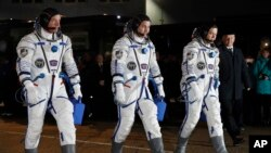 From left: NASA astronaut Jeff Williams, Russian cosmonauts Alexei Ovchinin, and Oleg Skripochka of Roscosmos, members of the main crew of the expedition to the International Space Station (ISS), walk to report to members of the State Committee prior to the launch of a Soyuz TMA-20M at the Russian leased Baikonur cosmodrome, Kazakhstan, March 19, 2016.