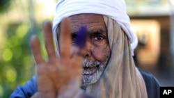 一埃及老人在宪法公决投票后显示自己沾墨水的手指