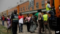 FILE - A policeman stands guard as people try to board a train on the Lagos to Kano route in Lagos, Nigeria.