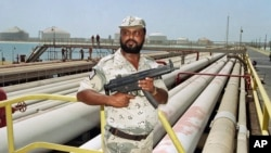 FILE - A security guard keeps watch over oil pipelines in Aramco refinery in Saudi Arabia.