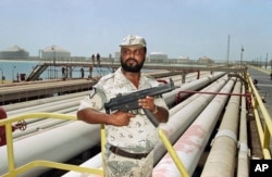 FILE - A security guard keeps watch over oil pipelines in Aramco refinery in Saudi Arabia in September 1990.