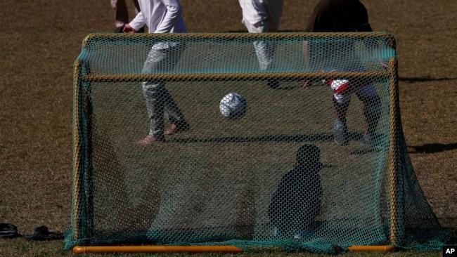 Pengungsi Afghanistan bermain sepakbola di taman bermain Institut Pengembangan Sumber Daya Manusia Nasional di Jincheon, Korea Selatan, 13 Oktober 2021. Para pengungsi muncul di hadapan publik untuk pertama kalinya sejak mereka tiba pada akhir Agustus. (Jeon Heon-kyun via AP)