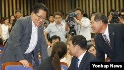 한국의 새정치민주연합 박지원 의원(왼쪽)이 4일 국회에서 열린 의원총회에서 7·30 재보선 당선 의원들과 대화하고 있다. 박지원 의원 등 5명은 김대중 전 한국 대통령 서거 5주기를 맞아 조화를 받기 위해 17일 방북할 예정이다.