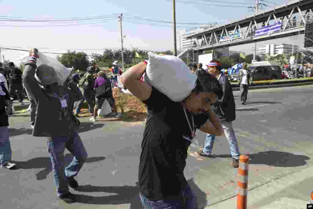 Etirazçılar yolları bağlamaq üçün qumla dolu torbalardan istifadə edirlər - Bankok, 14 yanvar, 2014