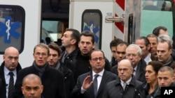 Presiden Perancis Francois Hollande (tengah), dikelilingi petugas keamanan saat tiba di luar lokasi penembakan di Paris (7/1). (AP/Remy De La Mauviniere)