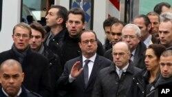 Presiden Perancis Francois Hollande (tengah), dikawal ketat oleh pasukan keamanan, mengunjungi kantor tabloid Charlie Hebdo pasca serangan, Rabu (7/1).