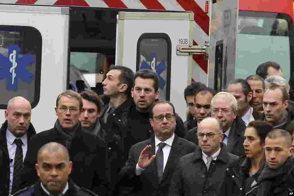 French President Francois Hollande, center, flanked with security forces gestures, as he arrives outside the French satirical newspaper Charlie Hebdo's office, in Paris, Jan. 7, 2015.