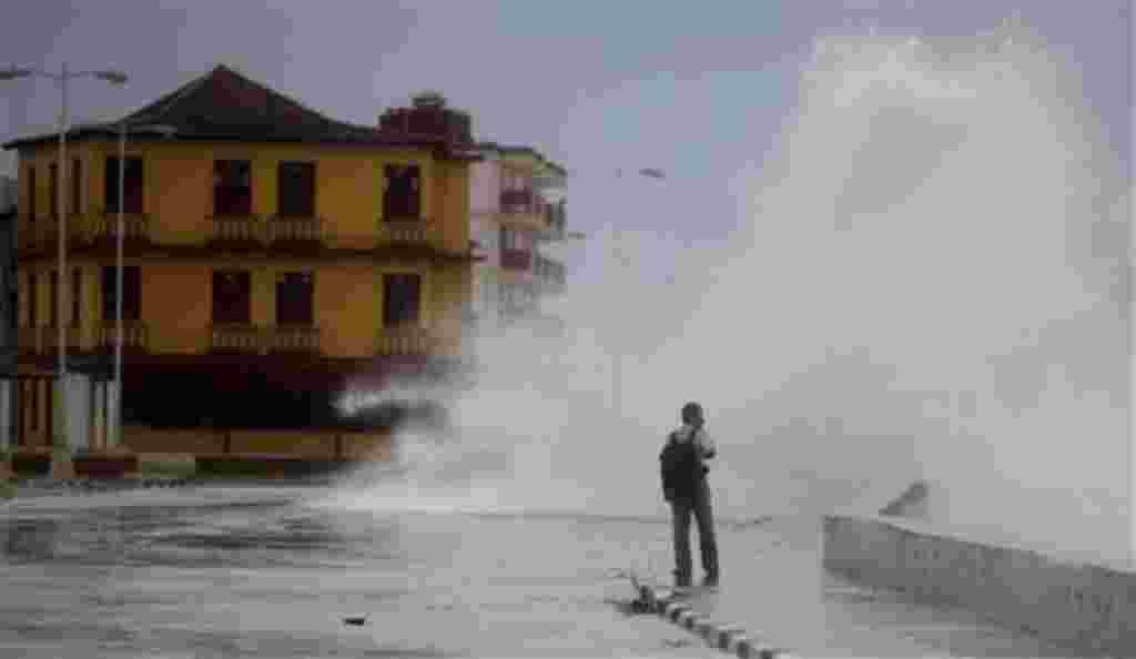 Un hombre entra en una ola que alcanzó la calle, como consecuencia del huracán Irene en Baracoa, Cuba, 24 de agosto de 2011.