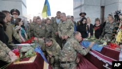 FILE - Ukrainian soldiers pay their respects during a memorial service for comrades killed in the conflict with pro-Russia separatists in Ukraine's eastern Donetsk region, in Independence Square in Kyiv, Ukraine, May. 26, 2016.