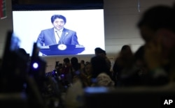 A projection screen shows Japanese Prime Minister Shinzo Abe deliver his speech during a plenary session at the Asia-Africa Summit in Jakarta, Indonesia, April 22, 2015.