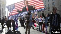 """Seorang pendukung Presiden AS Donald Trump membawa spanduk dalam demo """"Stop the Steal"""" di Washington D.C, untuk memprotes hasil pilpres AS yang diproyeksikan dimenangkan oleh capres Partai Demokrat, Joe Biden, Sabtu, 14 November 2020. (Foto: Reuters)"""