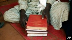 FILE - A Muslim man holds copies of the Koran at the central mosque in Yaloke, north of Bangui, Central African Republic.