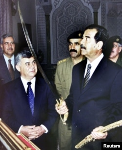 Former Iraqi president Saddam Hussein examines a sword as he received the Syrian prime minister Mustapha Miro in 2001.