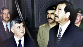FILE - Former Iraqi president Saddam Hussein examines a sword as he receives SyrianPrime minister Mustapha Miro in 2001.