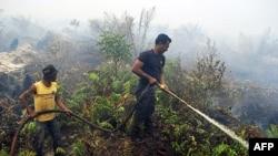 Nhân viên cứu hỏa đang dập tắt một đám cháy rừng ở Indonesia