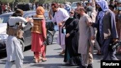 在巴基斯坦驻喀布尔大使馆附近,一名塔利班成员持枪对着抗议者。(2021年9月7日)