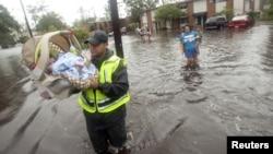 Un policía ayuda a evacuar un bebé de 21 meses, seguido por su madre en Slidell, Luisiana.