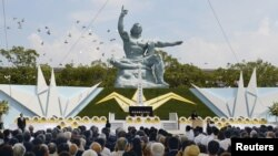 Doves fly over the Peace Statue in Nagasaki's Peace Park during a ceremony commemorating the 70th anniversary of the bombing of the city, in Nagasaki, Japan, in this photo taken by Kyodo, Aug. 9, 2015.