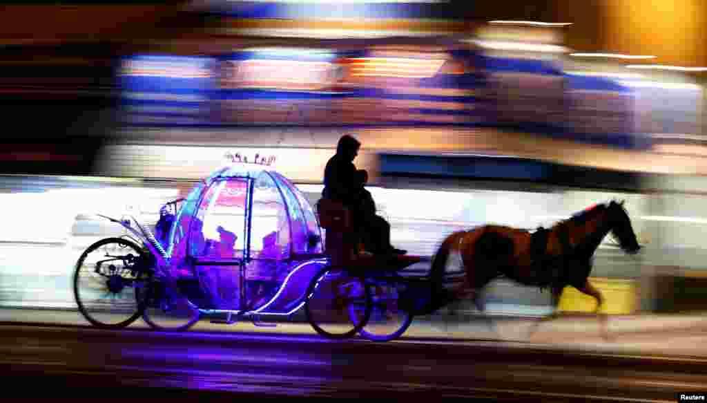 کودکانی که در یک کالسکه چراغانی در بلک پول انگلیس سوار شده اند.