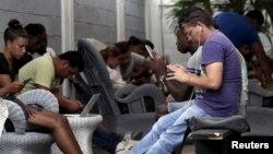 """Los jóvenes cubanos se conectan a internet gracias a la conexión gratuita afuera del estudio del artista cubano Alexis Leyva """"Kcho""""."""