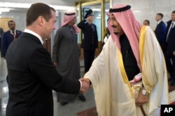 Russian Prime Minister Dmitry Medvedev, left, shakes hands with Saudi Arabia's King Salman during a meeting in Moscow, Russia, Oct. 6, 2017.