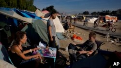 David Pirate, from left, Richard Ramirez, and Eric Koehler, who are homeless, pass time outside their tents after emptying a bottle of vodka as a group of cyclists ride along the Santa Ana River trail in Anaheim, California, Dec. 2, 2017.