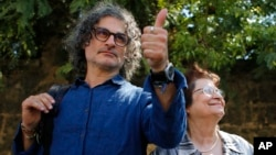 Lebanese film director Ziad Doueiri, left, gives a thumbs up next to his mother, Wafiqa, as he speaks to journalists after being released by a military court, in Beirut, Lebanon, Sept. 11, 2017.