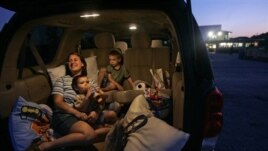 A family watches a movie at the Silver Moon Drive-In theater in Lakeland, Florida