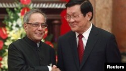 India's President Pranab Mukherjee (L) shakes hands with his Vietnamese counterpart Truong Tan Sang before their meeting at the Presidential Palace in Hanoi, Sept. 15, 2014.