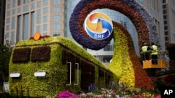 Workers on a platform install flowers on a display in a shape of a train to promoting the upcoming Belt and Road Forum (BRF) in Beijing, China, April 23, 2019.