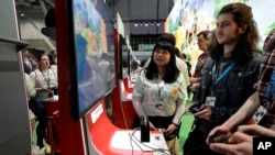 Visitors to the Pax East conference play the new Nintendo Switch video game Animal Crossing, Thursday, Feb. 27, 2020, in Boston. (AP Photo/Steven Senne)