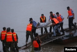 Rescue workers carry a body from the sunken ship in the Jianli section of Yangtze River, Hubei province, China, June 2, 2015.