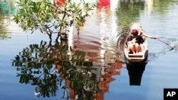 홍수로 잠긴 사원 앞을 배를 타고 지나가는 방콕 시민들